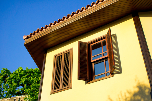 a picture of wooden Window Shutters installed on a traditional house