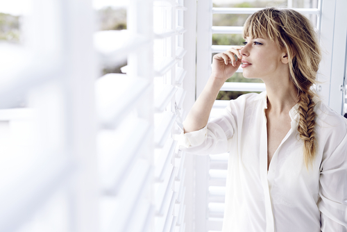 Image of a woman happy with her DIY plantation shutters in Sydney