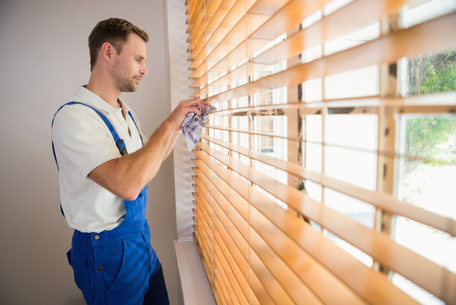 Image of a man cleaning blinds