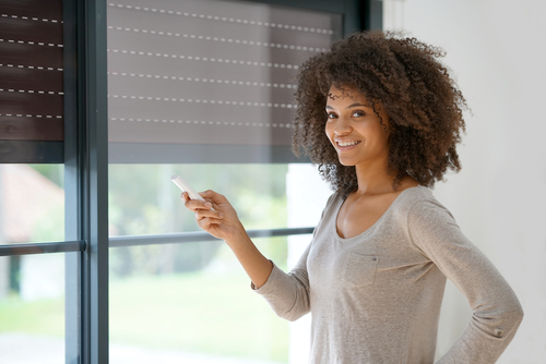 Image of a woman satisfied with her exterior window shutter