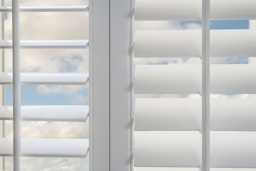 a close up picture of white plantation shutters