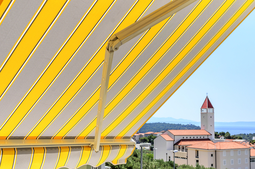Image of a yellow striped retractable patio awning